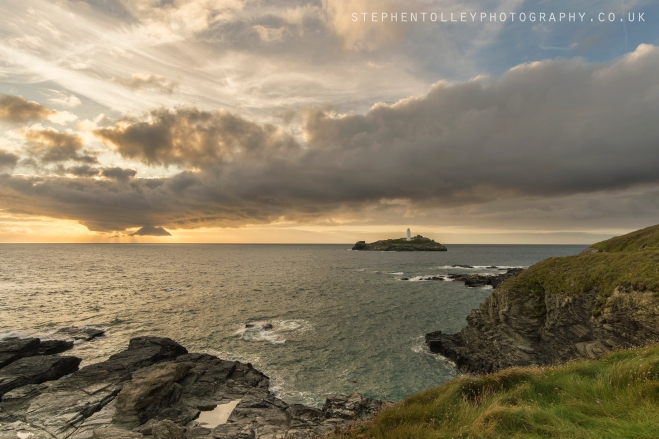 The Sun setting behind clouds at Godrevy